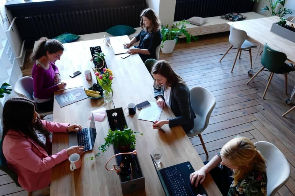 ludzie pracujący przy jednym długim biurku