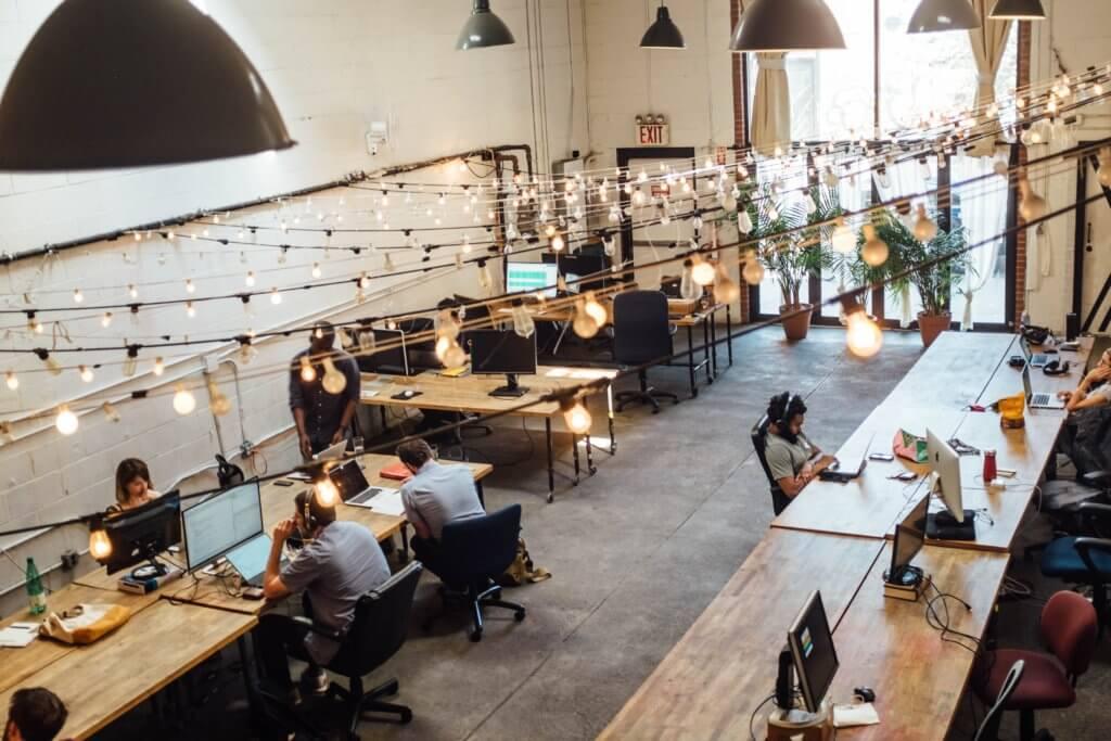 biuro coworkingowe, biurka, lampy, ludzie